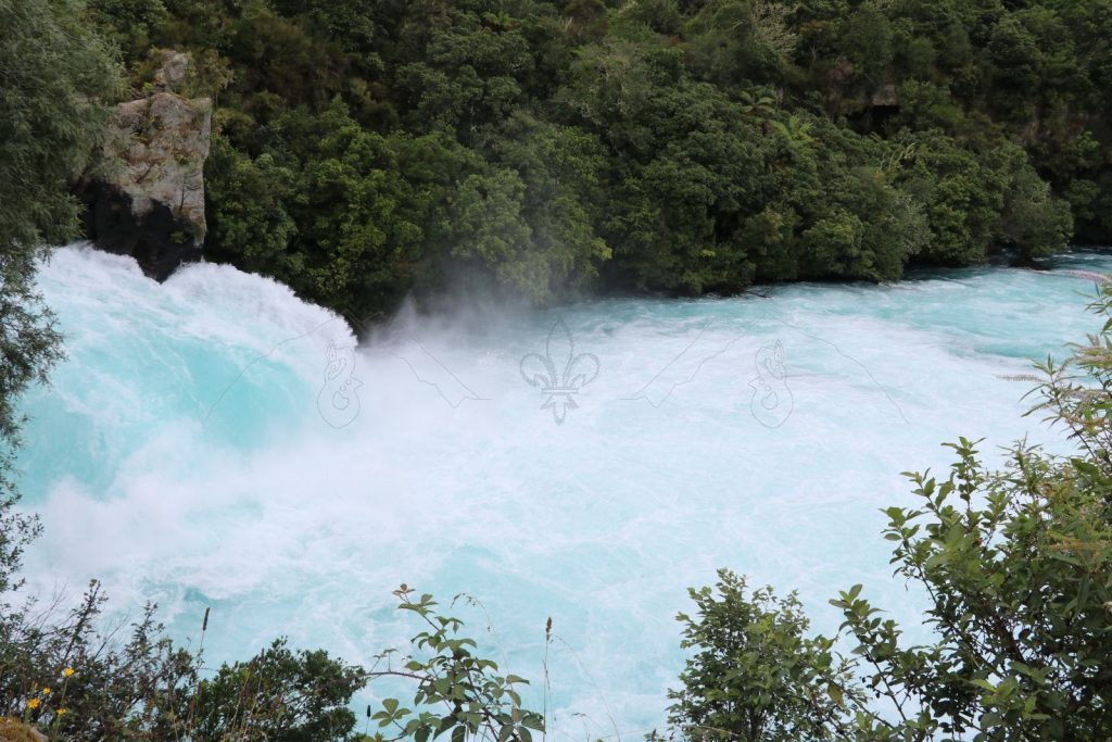 Die Gischt des larimarfarbenen Wasserfalles mischt sich mit vereinzelten Regentröpfchen.